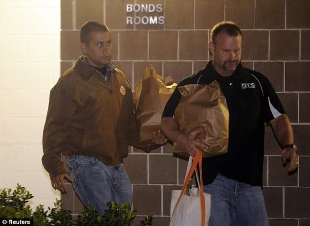 George Zimmerman to the left being escorted Sunday midnight by an unidentified man.