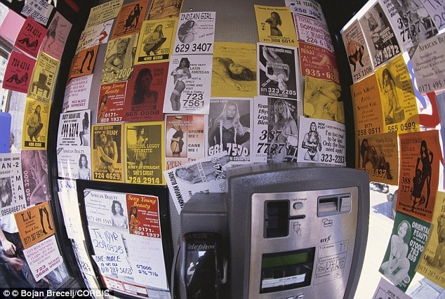 London pay phone overloaded with escort services.