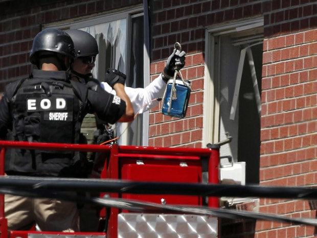"Members of law enforcement wearing body armor and helmets prepare to what ATF sources describe as a""water shot"" in the apartment of alleged gunman James Holmes Saturday, July 21, 2012 in Aurora , Colo. The ""water shot"" is exploded and used to disrupt the device. Authorities reported that 12 died and more than three dozen people were shot during an assault at a movie theatre midnight premiere of ""The Dark Knight Rises."" (AP Photo/Alex Brandon)"