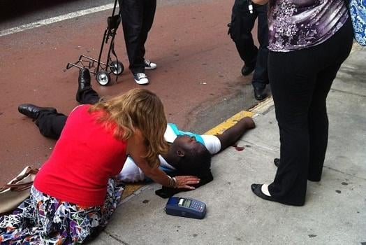 Empire State Building shooting. Shot pedestrian lies attended by fellow pedestrian.