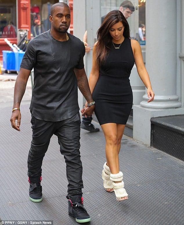 Kanye West with Kim Kardashian. Kim wears her monstosity without barely betraying a hint of self parody. Amazing....