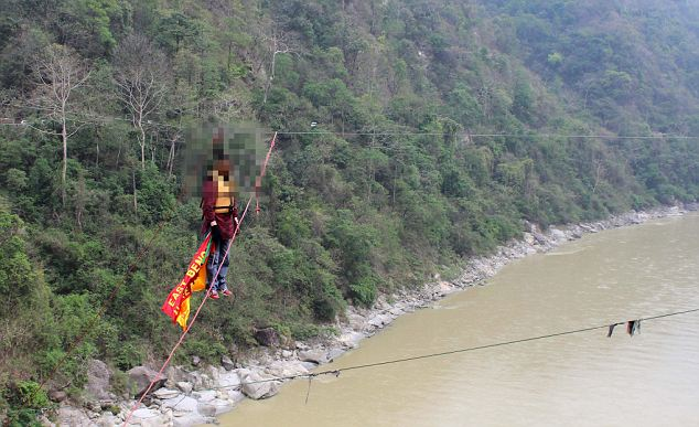 Indian Guinness world record holder Sailendra Nath Roy aged 50 hangs on a rope during his attempt to try crossing river Teesta with a rope tied between two hills with the help of his pony tail in Sevok on the outskirts of Siliguri.