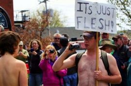 Anti topless male protestors belligerently protest their rights against pro female topless protestors.