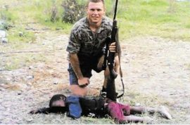 Who is the facebook racist user smiling, kneeling with rifle in hand over a lifeless little brown skinned boy?