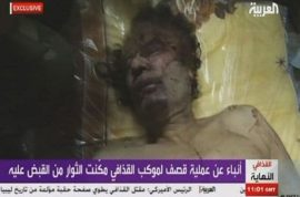 Muamar Gaddafi's body put on public display in shopping center meat locker freezer.