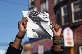 Mourners dance in the streets as Whitney's wake is held indoors.
