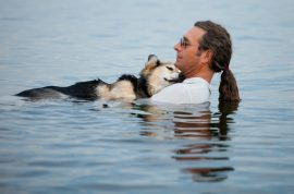 Picture of man craddling his dying athritic dog in Lake Superior 19 years after saving him goes viral.