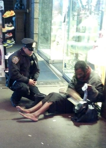 NYPD officer Lawrence Deprimo gives a homeless man boots. Photo via Jennifer Foster.