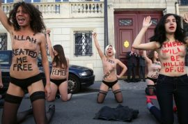 Femen activists stage topless protest in Paris to protest trial of three activists in Tunisia.