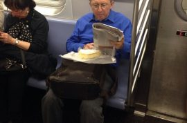 NYC Subway commuter revels in huge block of brie cheese.