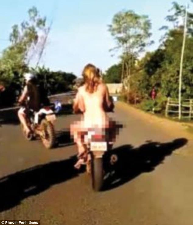 Trio riding motorbike naked through Cambodia