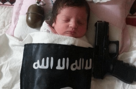 Here is a baby sleeping beside handgun and grenade underneath ISIS blanket