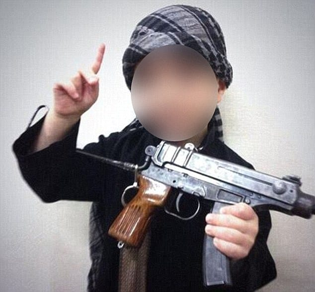 baby sleeping beside handgun and grenade underneath ISIS blanket